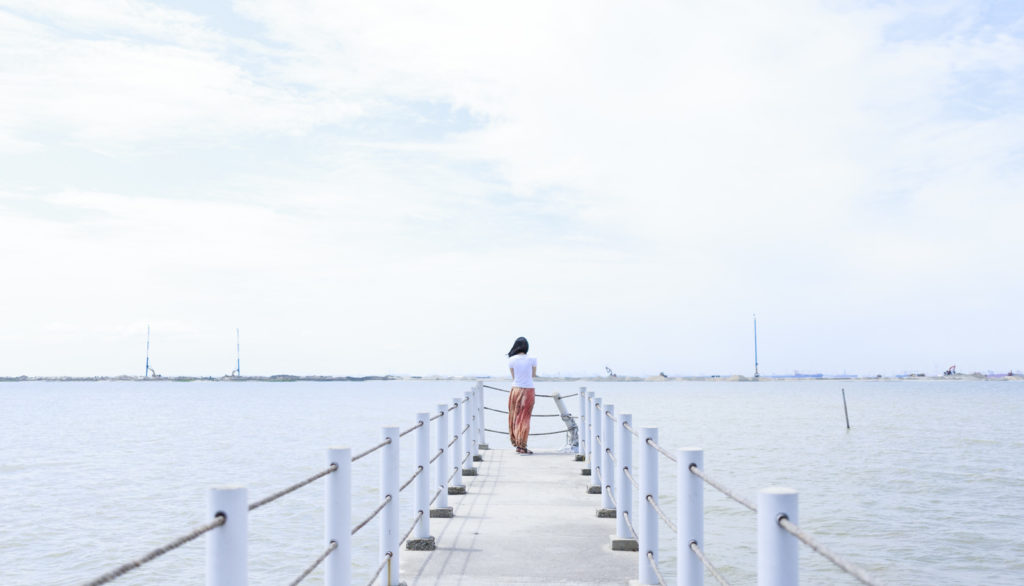 Woman walking out to the edge of a relaxing dock over water
