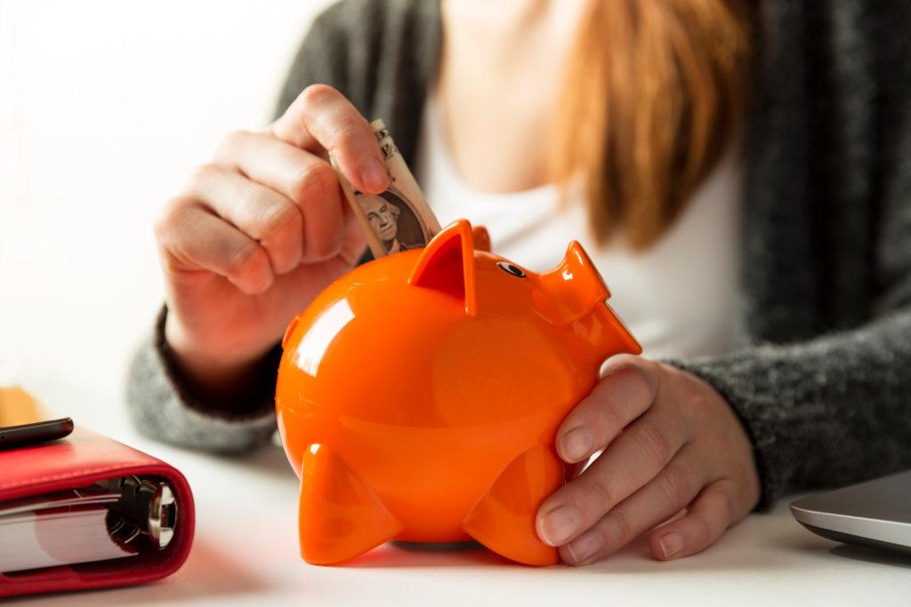 Woman putting a dollar into a piggy bank